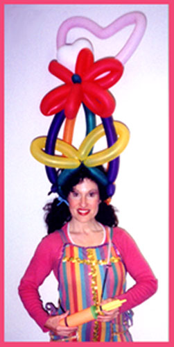 Balloon artist Daisy Doodle wearing a balloon hat she twisted for herself as she performed kids balloon entertainment at a street fair in Manhattan NY