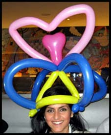 The balloon heart hats twisted by Daisy Doodle come in a wide variety of colors, to match the birthday girl's outfit