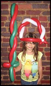 This child is wearing a holiday balloon hat and twisted balloon sword at a Xmas party in nyc