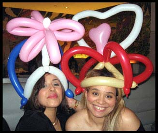One lady is wearing the balloon heart crown and the other lady chose the flower balloon hat by balloonist Daisy Doodle to celebrate their special day