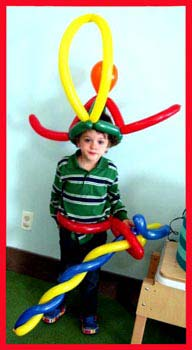 A kid shows off his costume made from twisted balloons by balloon artist Daisy Doodle