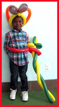 Boy poses with his twisted balloon super sword, belt and balloon hat at corporate party in CT