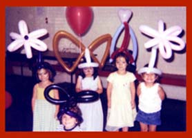 Childrens wearing a variety of balloon hats made by balloon twister Daisy Doodle for their kids party entertainment