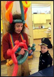 Balloon twister Daisy Doodle deep in concentration as she makes a dinosaur balloon hat for this boy at a Purim Party in Manhattan