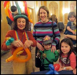 Kids are excited  as they wait for a balloon hat or balloon animal from balloonist Daisy Doodle at the Jewish Center Purim Party