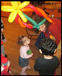 This little girl looks in awe at balloon artist Daisy Doodle making balloons at the purim party she is attending in nyc