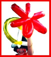 A girl shows off her fancy balloon hat made by Daisy Doodle for balloon entertainment for a festival in New York