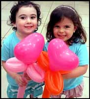 Balloon sculptor Daisy Doodle twisted heart flower balloons for these girls at their summer camp party in Manhattan