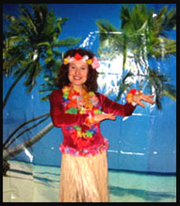 Hula dancer Daisy Doodle poses in front of Hawaiian backdrop at party in New York City