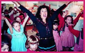 Children follow the words of the song and lift their arms for YMCA dance party entertainment in New York