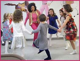 Kids join hands to dance in a circle during the chorus of the Chicken Dance