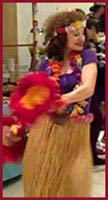 Hula dancer Daisy Doodles shakes her feathered gourds in her opening dance number at a kids birthday party