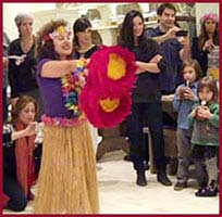 Hula Dancer Daisy Doodles strikes a pose with her feathered gourds to end her opening hula dance number at a child's birthday party in Manhattan NY