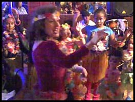 Hula dancer Daisy Doodle teaches a group of kids how to perform a Hawaiian hula dance at a girl's birthday party in Brooklyn New York
