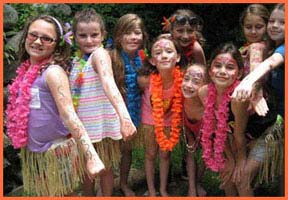 At beginning of hula dance birthday party luau in Westchester NY, girls are facepainted by hula dancer Daisy Doodle before their hula dance lesson