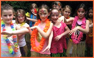 After their hula dance lesson with hula dancer Daisy Doodle, girls demonstrate the arm movements they learned at this tropical Hawaiian luau party
