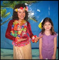 Birthday girl poses with hula dancer Daisy Doodle in front of palm trees beach backdrop for her Hawaiian luau birthday party before hula dance lesson