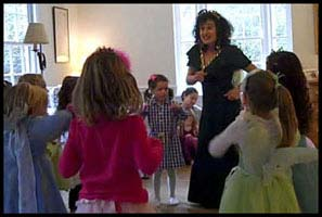 Princess Daisy shows children how to shake their hips as directed by the lyrics of the chicken dance music
