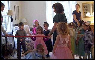 Kids try to dance under limbo string without falling down at princess birthday party