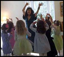 Daisy Doodle has children lift their arms high to twist to popular birthday party dance music