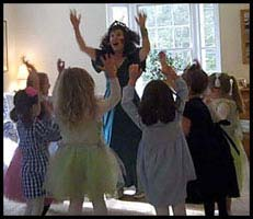 Children raise their arms to dance as instructed by princess Daisy Doodle