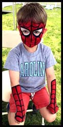 Boy gets spiderman face painting and arms body painted with spider webs at kids party in Long Island NY