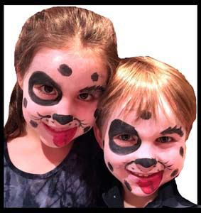 Brother and sister face painted as dalmations at company party in Manhattan NY