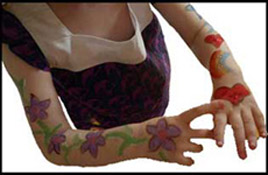 A girl gets both arms face painted as part of face and body painting party entertainment