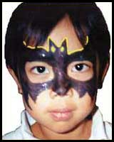 Boys enjoy being face painted as superheros, like this Batman facepainting at a kids party in Bronx ny
