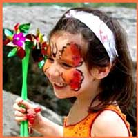 A girl flits about with her face painted as a butterfly at a birthday party in central park, ny.  Watch out for the pond!