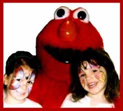 Elmo approves of Daisy Doodle's butterfly facepainting of several kids at a birthday party.