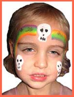 Rainbow with skeleton heads adorn the face of this girl at a halloween birthday party