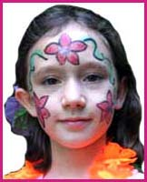 Facepainter Daisy Doodle paints flowers on this party girl's face to match the flowers in her lei and in her hair.