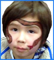 Boys like to be facepainted as snakes and this child chose a giant cobra snake. Hope he doesn't scare the little kids!