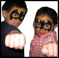 Boys facepainted as batman superheroes strike a dramatic pose at childrens party at a private club in new york city