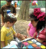 Face painter Daisy Doodle is busy face painting kids at an outdoor birthday party in Central Park NY