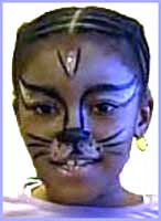 Childrens party facepainter Daisy Doodle turns a girl into a cat with her facepainting skills.