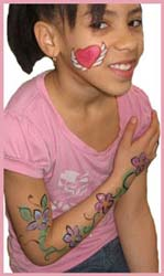 An older girl gets her face painted with a heart and gets body painted with flowers for a festive party look in connecticut
