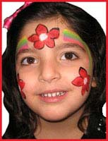 This child is facepainted as a holiday poinsetta princess at a holiday Christmas party in new york city.
