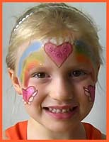 A variation of a rainbow heart princess is face painted on this girls face at a street fair in nyc.