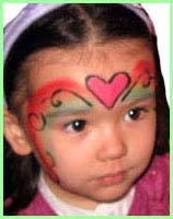 A girl gets facepainted as a rainbow princess at a childrens birthday party face painting session in nyc