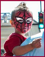 Face painter Daisy Doodle turns a little boy into Spiderman at a street fair in Long Island NY