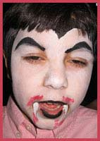 Boys like to be facepainted as scary vampires for halloween parties in bronx, new york.  Watch out for those fangs!