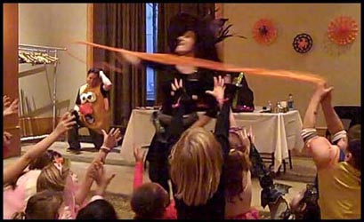 Kids reach up to grab the flying streamer that opens the halloween magic show at this childrens halloween party in nyc