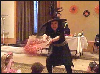 Daisy Doodle Diabolica scares the kids with her broomstick as part of the opening number for her Halloween magic show in nyc.