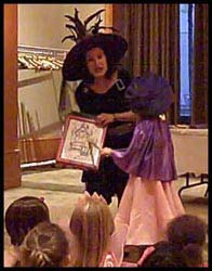 A child volunteer helps magician Daisy Diabolica with this halloween magic trick