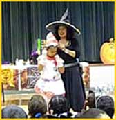 Childrens Halloween magician Daisy Doodle puts a hat on her volunteer to complete this halloween magic trick.