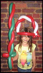 Girl wears a balloon twisted hat and brandishes a balloon sword at her Christmas party