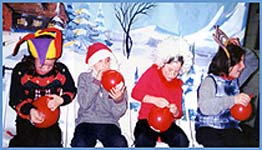 Children blowing up balloons for a contest in the holiday party magic show in new york city