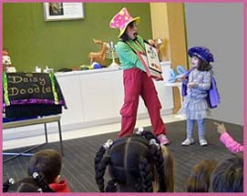 Kids holiday magician Daisy Doodle showing children the magic painting at the office Christmas party entertainment in new york ny